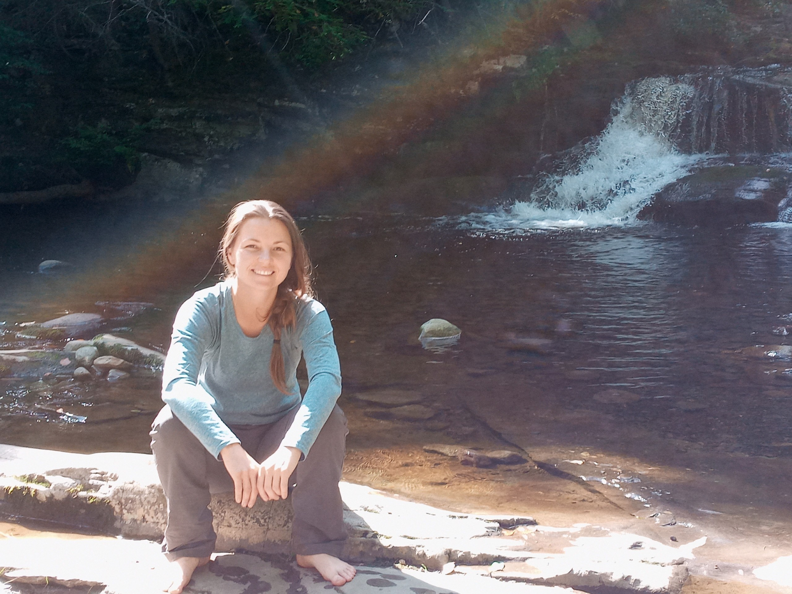 Image of Kate sitting on a rock by a stream