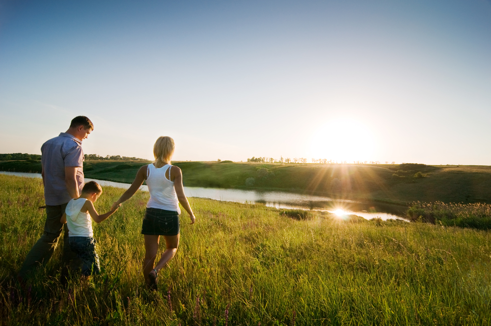 Family running to sunrise