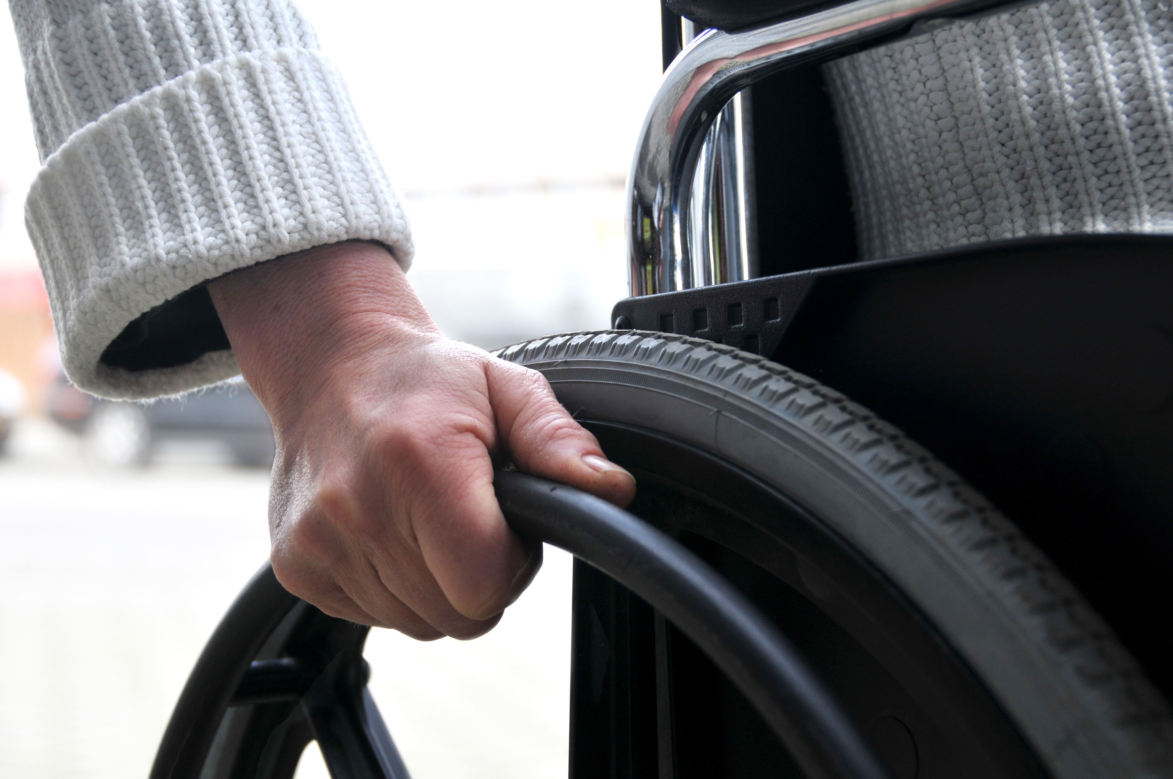 Close up of a hand rolling a wheelchair wheel