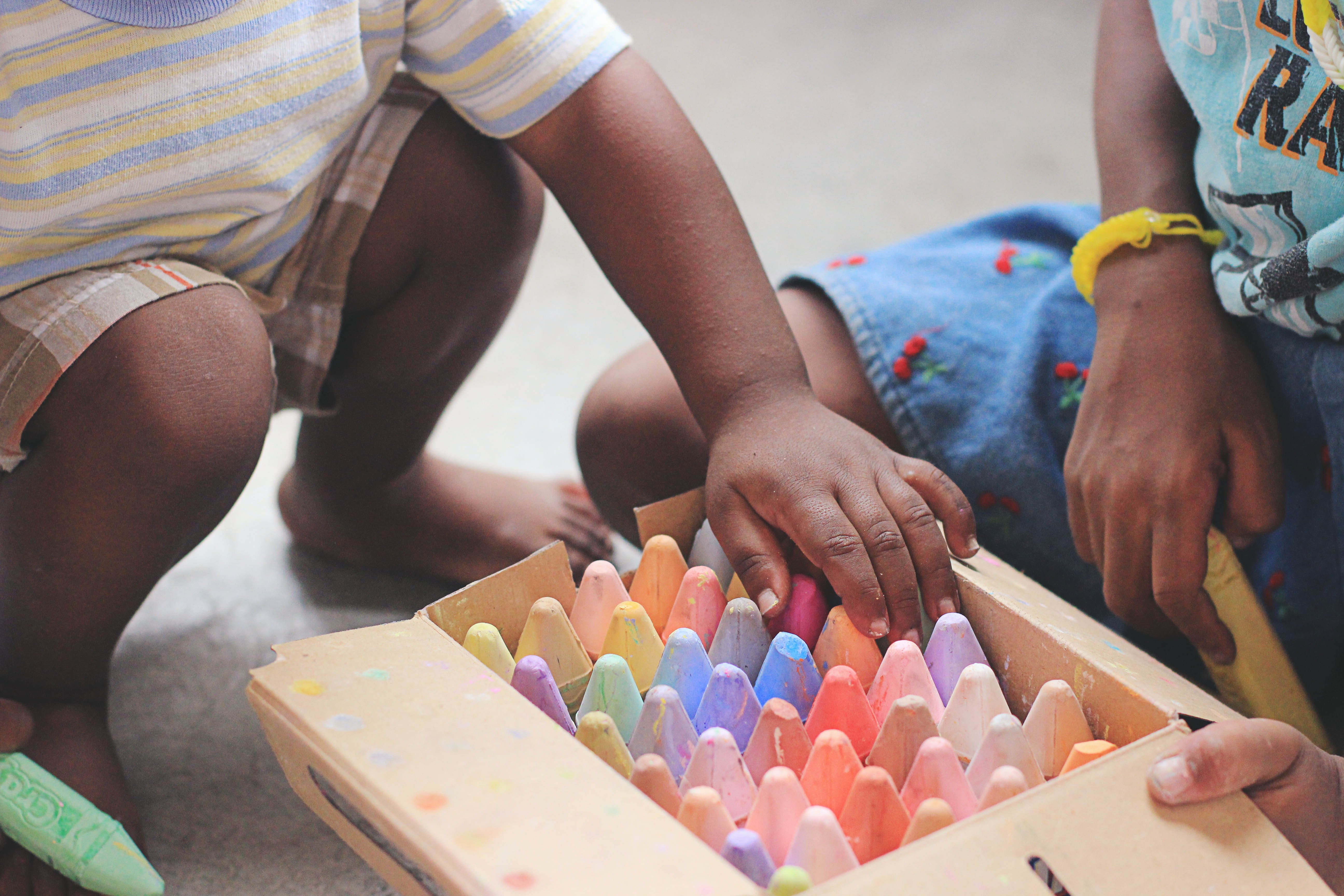 Two children playing with a big colourful box of chalks