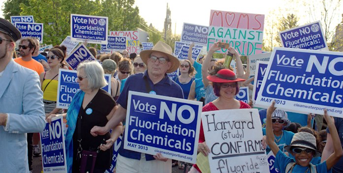 People marching with signs expressing opposition to fluoridation.