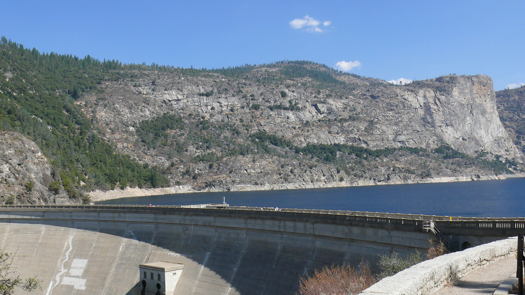 A large concrete dam stretches across the bottom of Hetch Hetchy reservoir