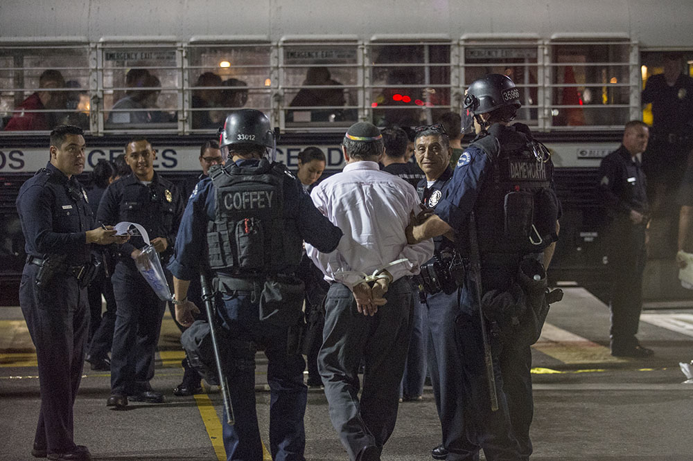 Rabbi Dr. Aryeh Cohen, center, being taken to the LAPD bus following his arrest in front of the LA Chinatown Walmart Neighborhood Market on November 7, 2013. Photo Credit: Zachary Conron