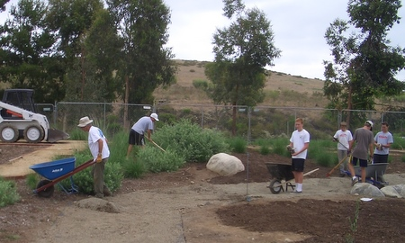 Star volunteer Pete and a group of boys prep the dry creek