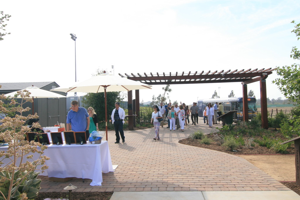 Guests step off of an Anteater Express shuttle into the garden and view our silent auction items.