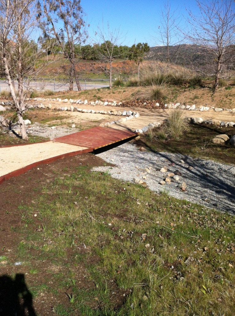 Another bridge that provides a pathway over the dry creek bed.