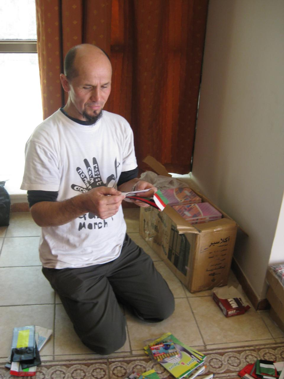Les reads messages from American kids to kids in Gaza while preparing backpacks of supplies for delivery