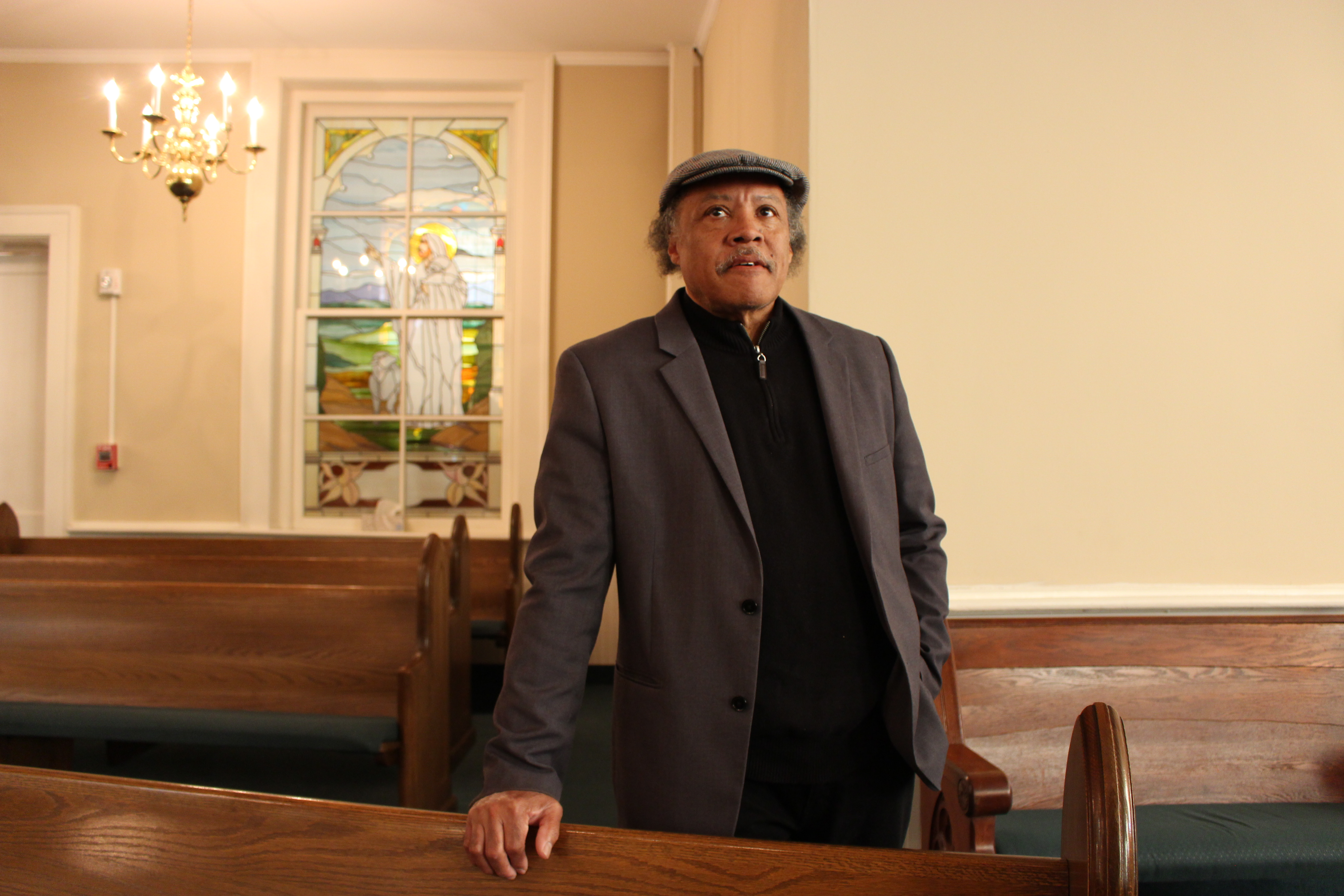 Elder Roy Harris stands in his church, Mt Zion Missionary Baptist Church for a portrait. He rests his right hand on a pew and looks beyond the camera towards the front of the worship hall. He is wearing a grey suit, black sweater, and a grey flat cap hat.