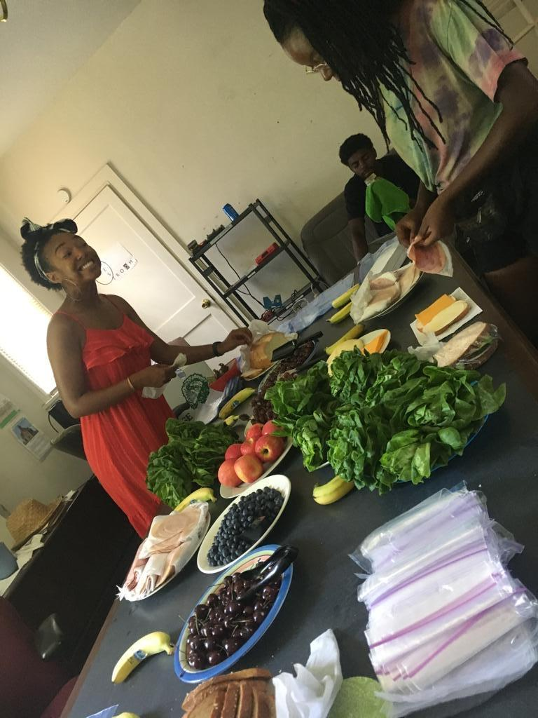 Black woman smiling while placing food on long table with beautiful fresh herbs and produce.
