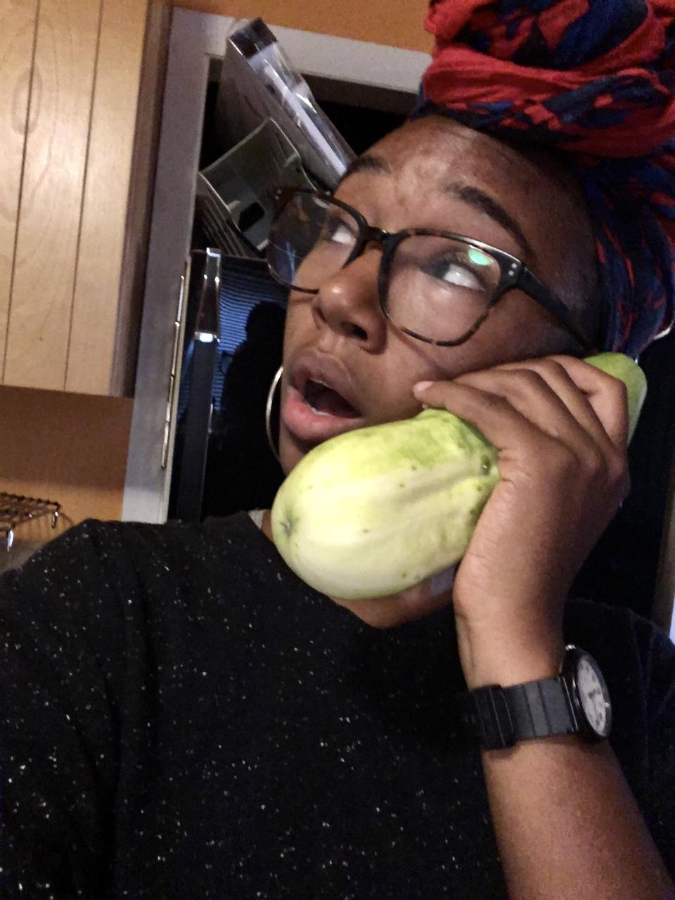Black woman playfully holding large pale green cucumber to her ear like a phone!