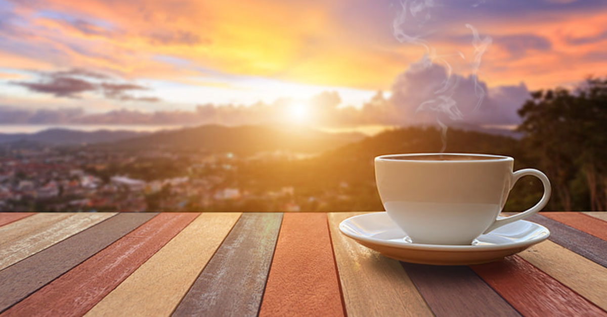 Mission and Vision - photo of a steaming cup of coffee outdoors with a view of the sunrise. Coffee Party USA.