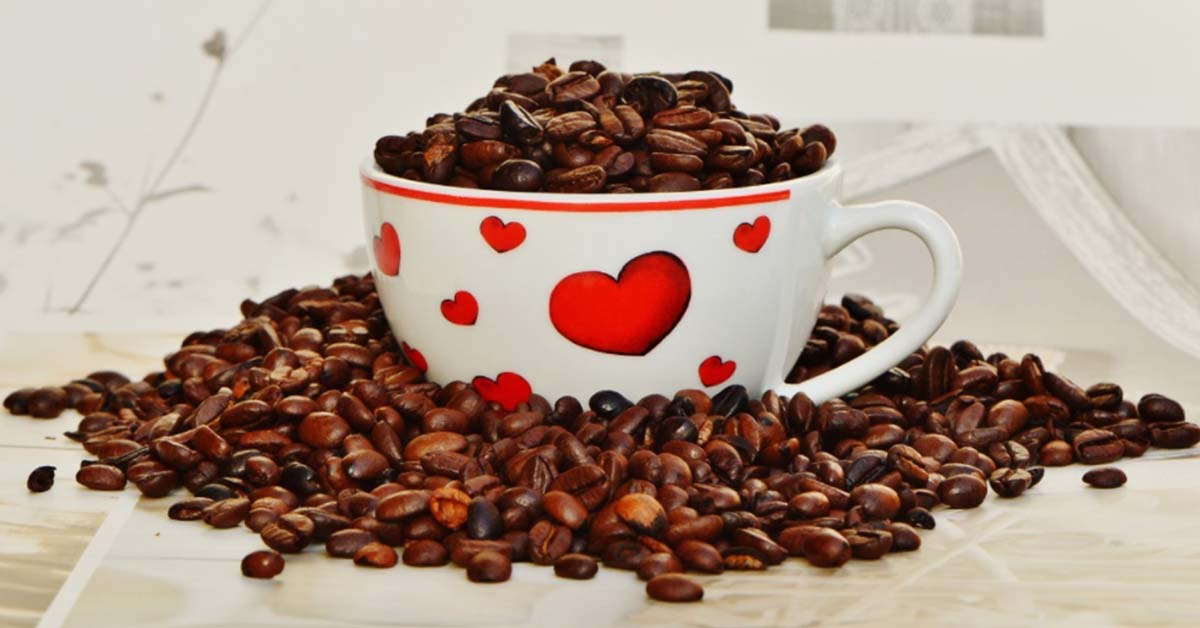 Photo of coffee cup overflowing with coffee beans and decorated with hearts.