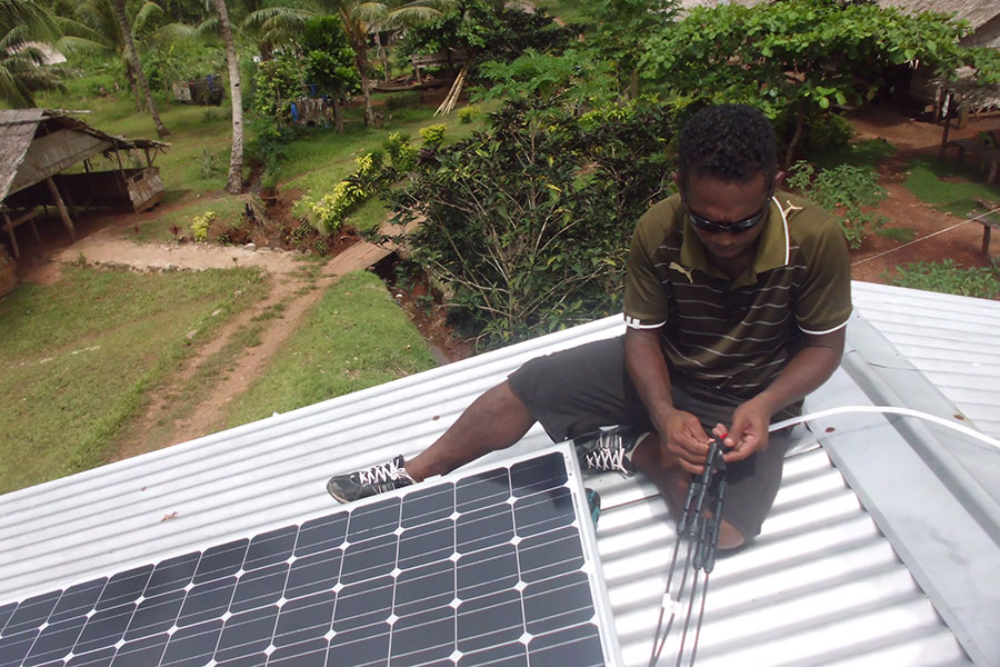 Holland Sikou installing solar panels on the roof of a school in Solomon Islands.