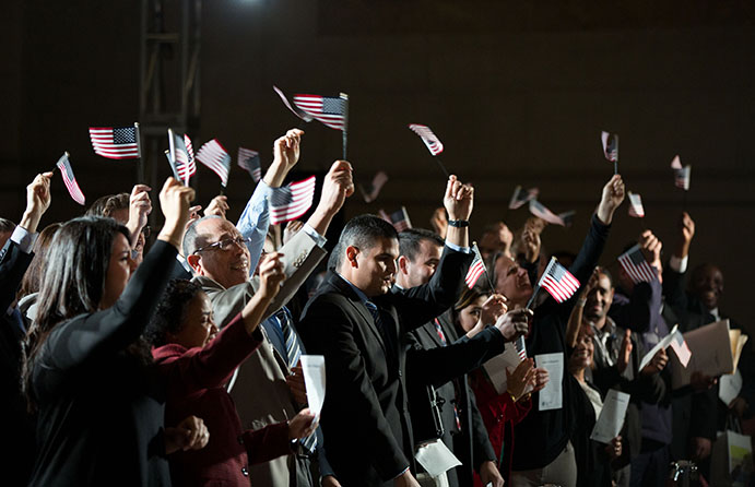 Crowd of people at night time waving american flags.