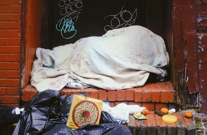 Person bundled in blankets in front of garbage.