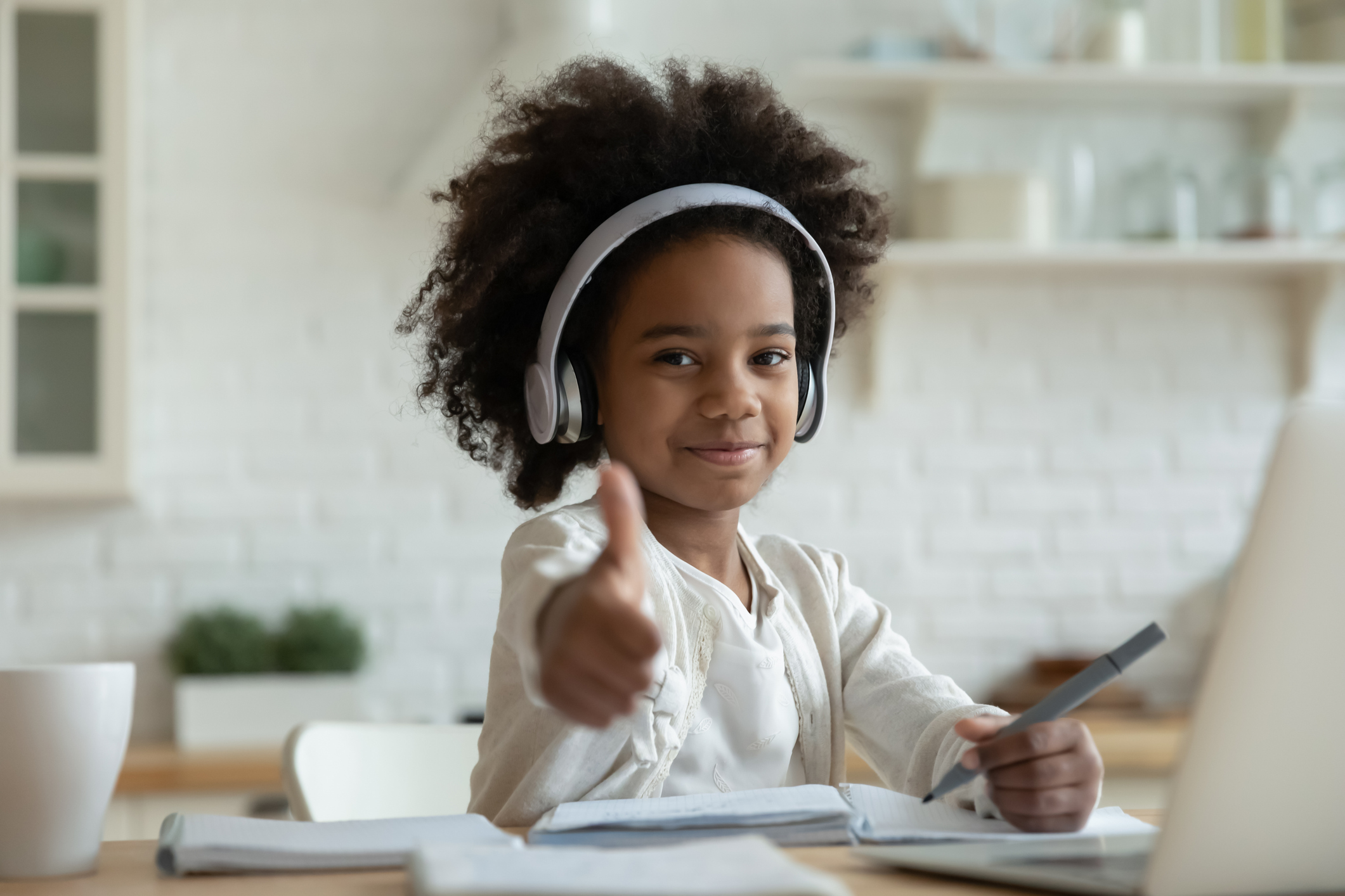 child at desk with headphones