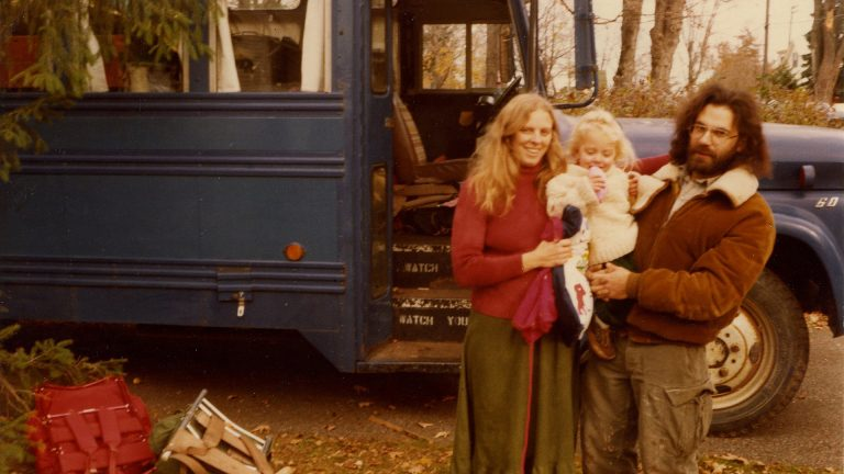 Parents holding child in front of school bus - from the movie Hippie Family Values