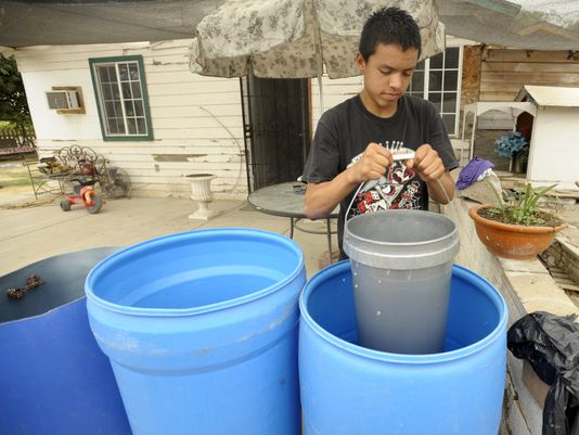 residents who lack water fill up barrels at neighbors' or relatives' houses
