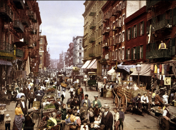 photo of many people, vendors, horse carts, etc. in city street