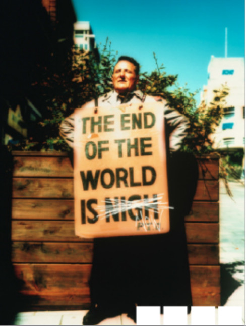 photo of man wearing a sign 'THE END OF THE WORLD IS NIGH (crossed out) NOW'