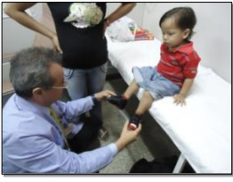image of doctor with hands on feet of young patient