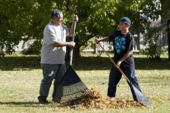 photo or two people raking leaves together