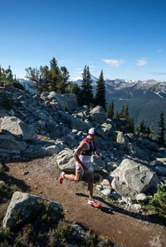 ultramarathon runner on downhill trail among boulders