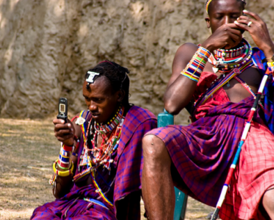 image of two tribesmen in native dress using mobile telephones