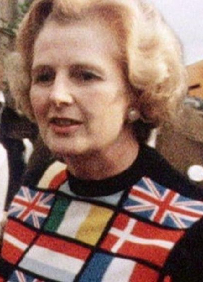 photo of Margaret Thatcher wearing a sweater bearing a dozen or more national flags