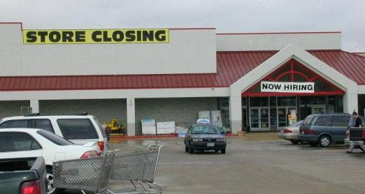 photo with 'STORE CLOSING' and 'NOW HIRING' banners both hung outside same store