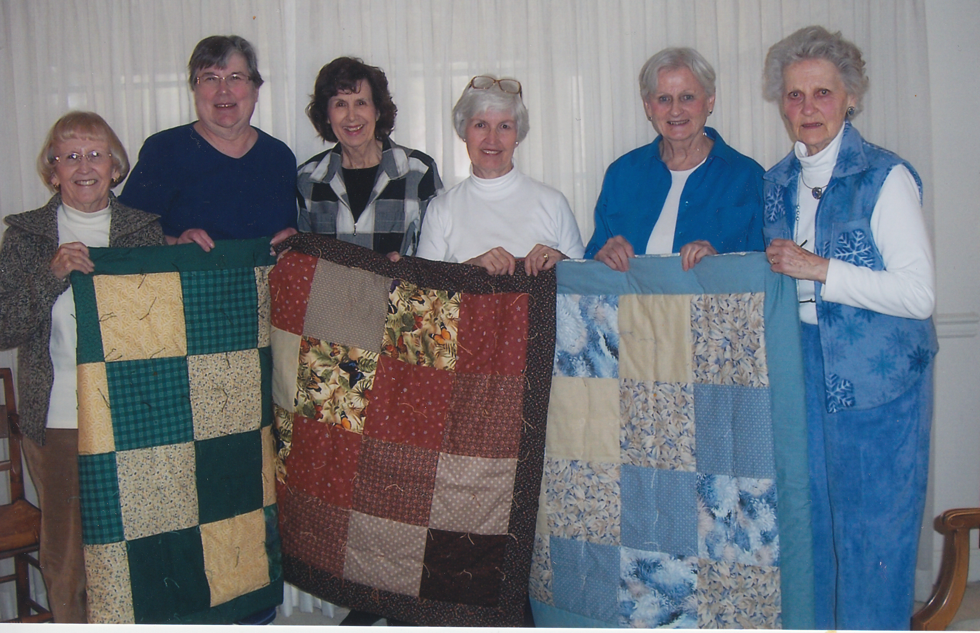 photo of quilters with quilts