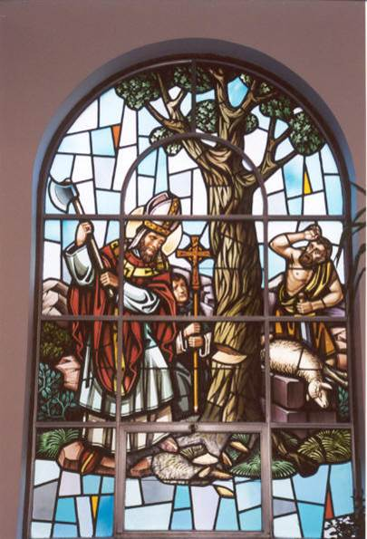image in stained glass window of St. Boniface chopping at a tree