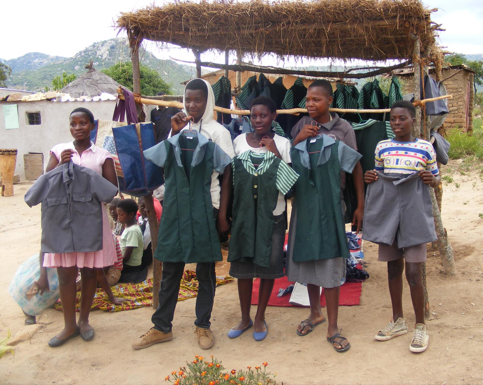 photo of teenagers holding uniforms