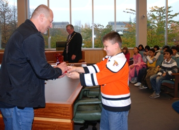 CUPE 23 president Rick Kotar accepts gift from a Stride Elementary School pupil, as Burnaby Mayor Derek Corrigan looks on, during a school field trip to Burnaby City hall yesterday.