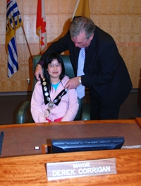 Corrigan speaks to Grade Four and Five pupils, and places the mayoral sash on 'Acting Mayor' Jacqueline Sheh.