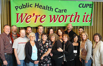 """Some of the delegates at the Community Health bargaining conference pose under a banner featuring the bargaining conference theme, """"We're worth it!"""""""