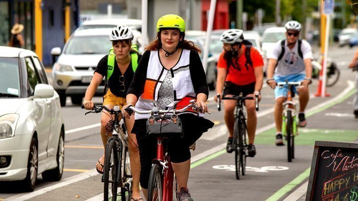 Several people riding bikes in everyday clothes.