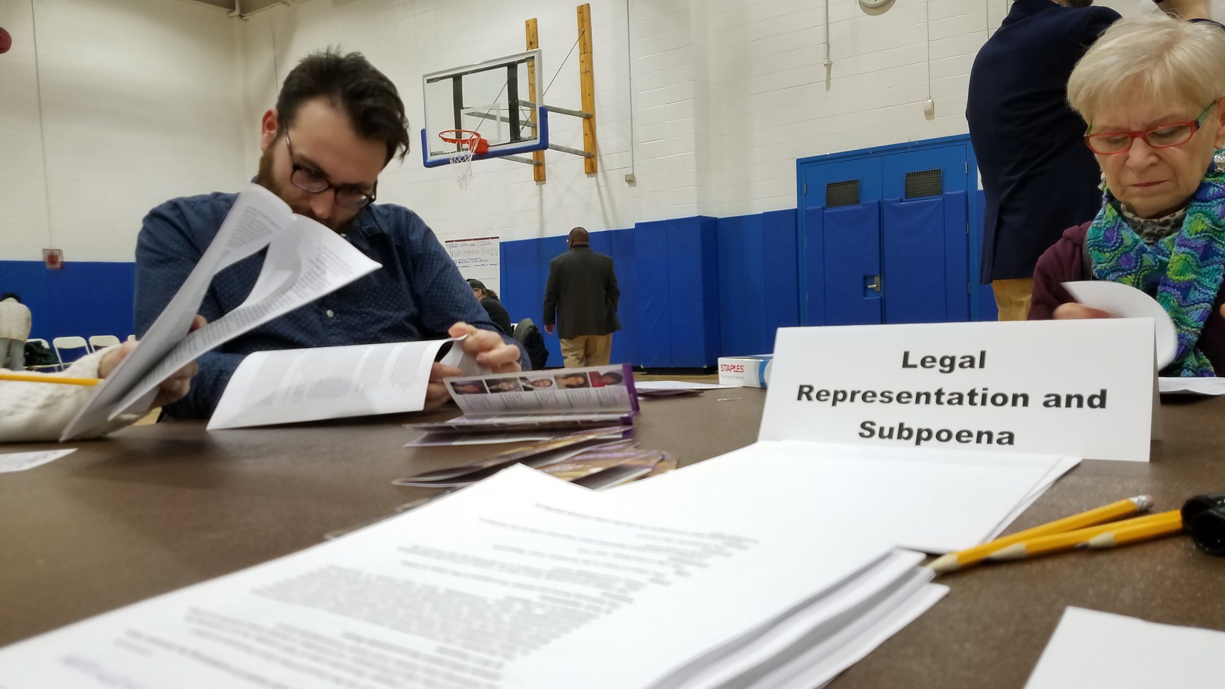 Two people sitting at a table in a gymnasium reading about the Police Accountability Board