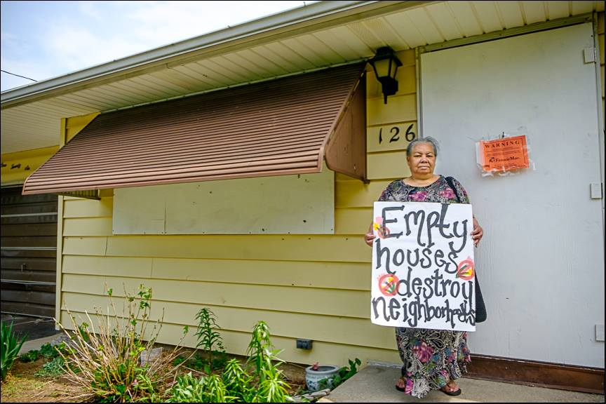 A woman standing in front of a boarded up house with a sign that says \