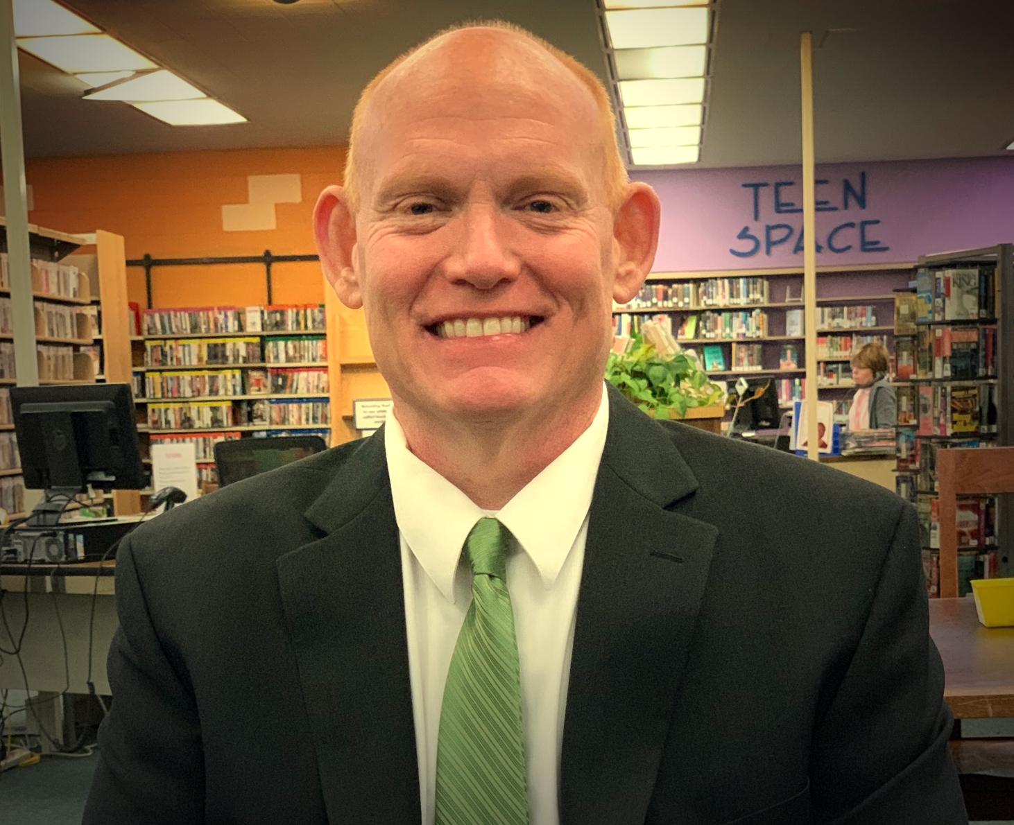 A white man wearing a suit with a green tie in a library.