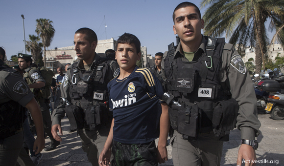 Israeli border policemen arrest a Palestinian child