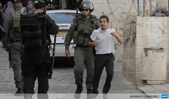 Israeli border guard detains a Palestinian youth