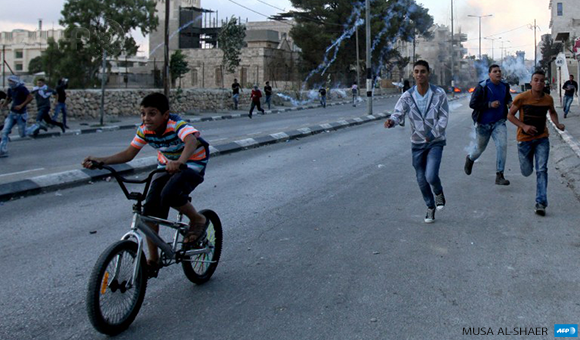 Palestinian youths take cover near Bethlehem on October 6
