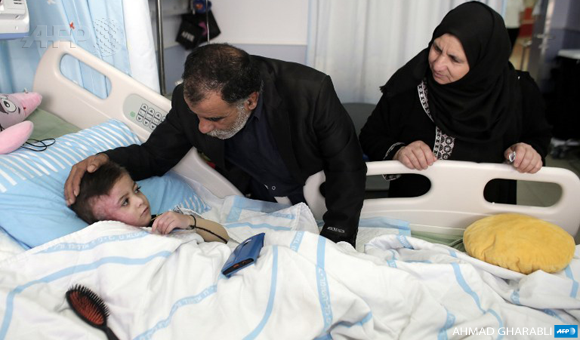 Four year-old Ahmed Dawabsha receives a visit from his maternal grandparents in hospital on December 5, 2015 where he is being treated for burns after his family house was firebombed by Jewish extremists on July 31, in the Israeli-occupied West Bank village of Duma. AFP PHOTO / AHMAD GHARABLI