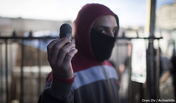 A Palestinian youth shows a black sponge bullet shot by the Israeli police.