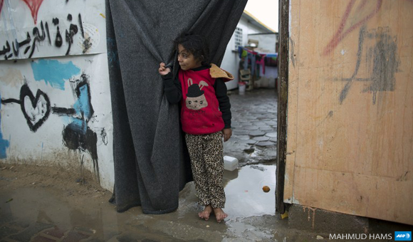 A Palestinian girl stands barefoot outside temporary housing during a winter storm in Beit Hanoun in the northern Gaza Strip on January 24, 2016.