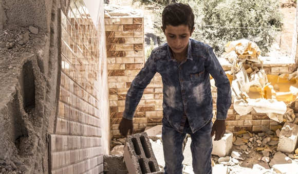 A boy looks through the rubble of Ahmad Makhamra's apartment building after Israeli forces carried out a demolition on August 4, 2016. (Photo: DCIP / Cody O'Rourke)