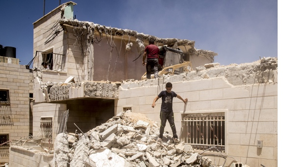 Two children walk over the rubble of Mohammad Musa Eid's apartment. (Photo: DCIP / Cody O'Rourke)