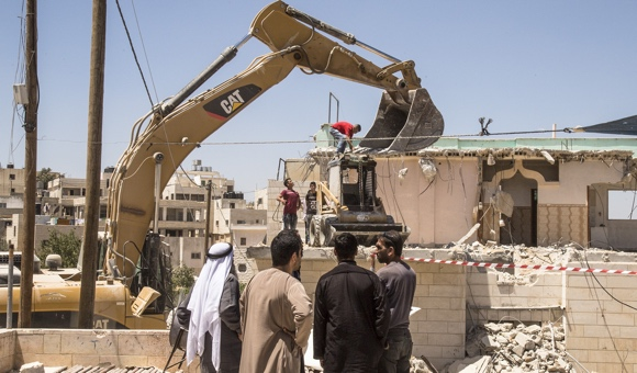 An excavator clears the rubble from Mohammad Musa Eid's apartment after Israeli forces demolished it. (Photo: DCIP / Cody O'Rourke)
