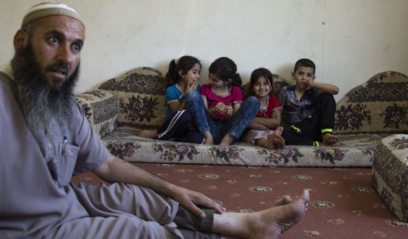 Mohammad Musa Eid Makhamra, father of accused attacker Khaled, sits with his two children and two nieces, in his home in Yatta before it was demolished. (Photo: DCIP / Cody O'Rourke)